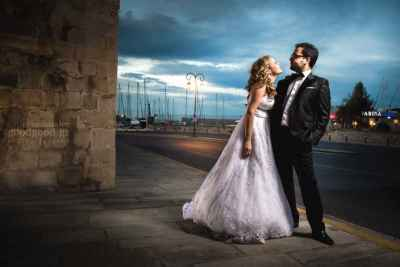 Photograph of a bride trying to kiss the groom while he's drawing back, docks, Heraklion, Crete, Greece