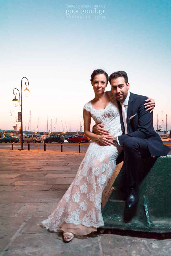 Photograph of a newly wed couple siting on a bollard at the Heraklion marina