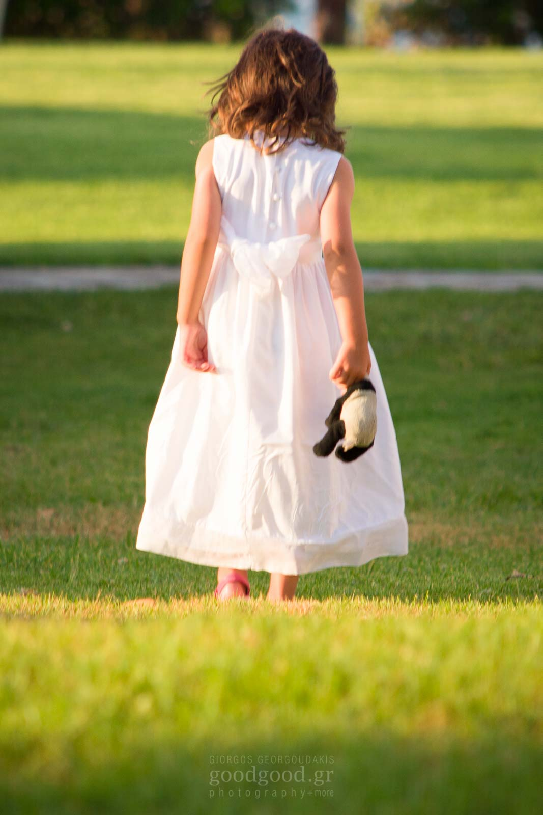 Baptism photo of a little girl standing on the grass holding a doll