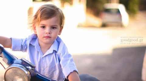 Ένα αγοράκι παριστάνει οτι οδηγεί μηχανή την ημέρα της βάπτισης του