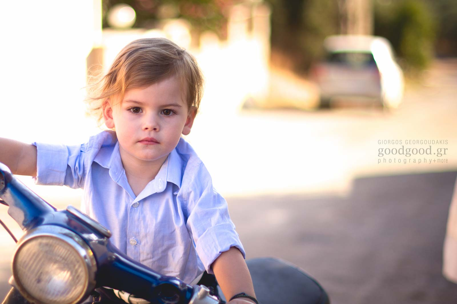 Little boy pretending to ride a motorbike in his baptism day
