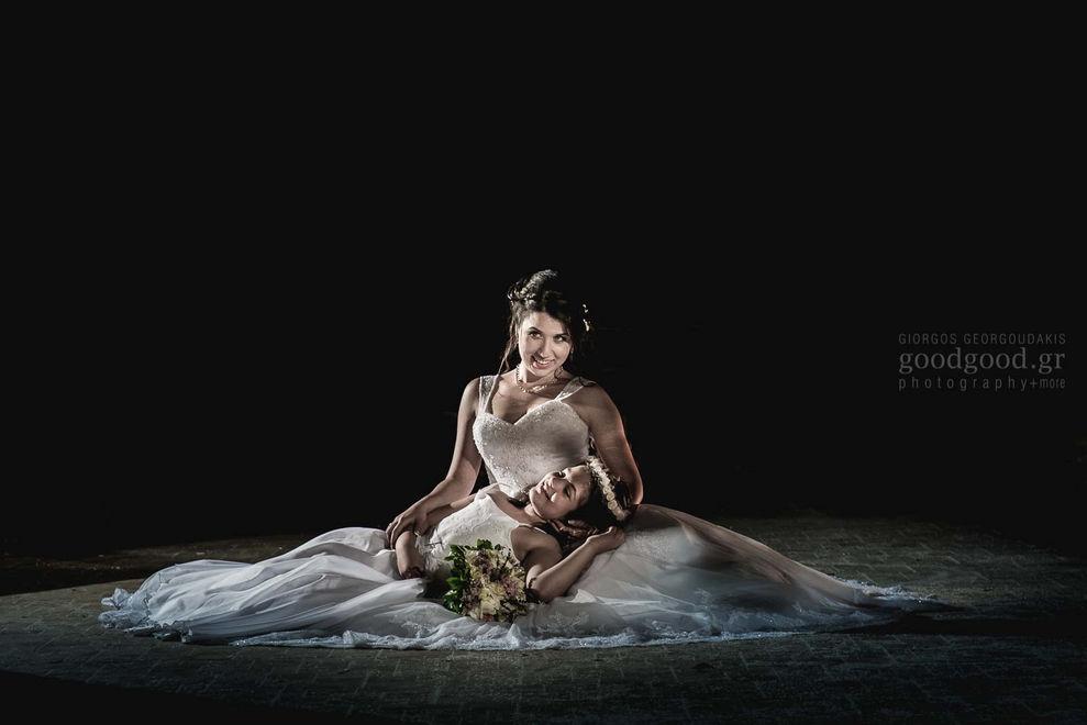 Νύφη κάθεται στο πάτωμα και κρατάει ένα παρανυφάκι στα χέρια της