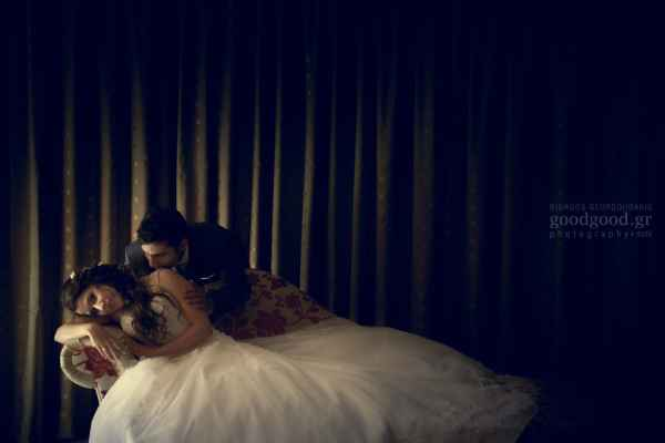 Bride laying in a daybed while the groom softly kisses her on the shoulder