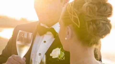 Φωτογραφία ενός γαμπρού και μίας νύφης να πίνουν την πρώτη τους σαμπάνια μετά τον γάμο στο ηλιοβασίλεμα
