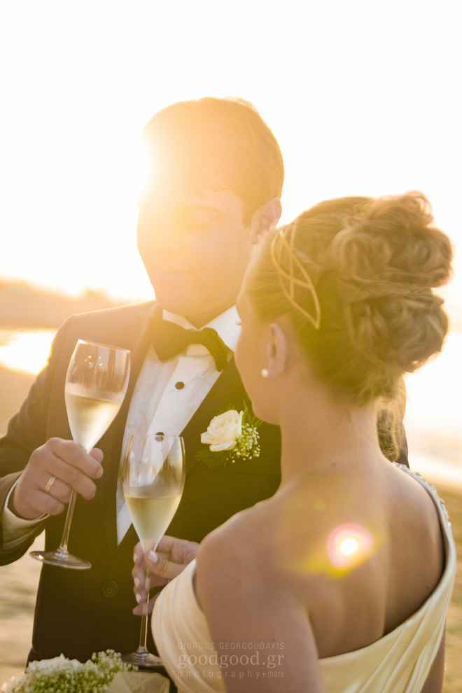 Photograph of a groom and a bride having their first champagne after the wedding in the sunset