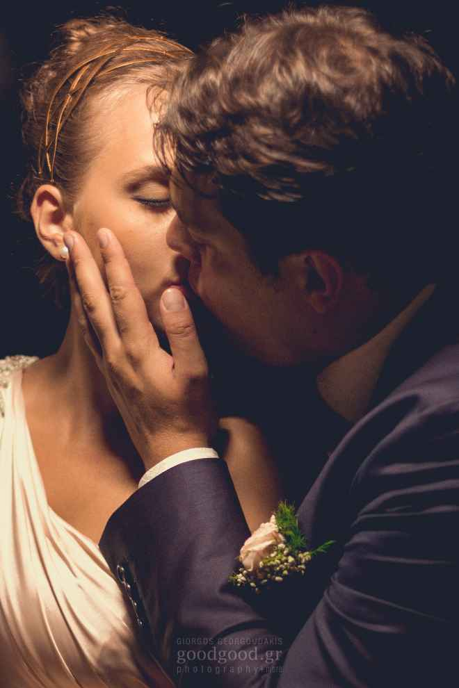 Photograph of a groom softly kissing the bride under an icelight