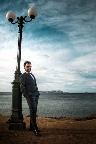 Photograph of a groom leaning on a light pole near the sea at Gouves of Heraklion, Crete