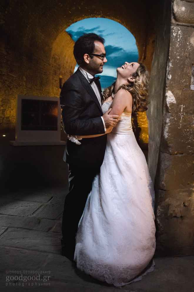 Photo of a groom and a bride standing and laughing against the wall of the old shipyard at Heraklion