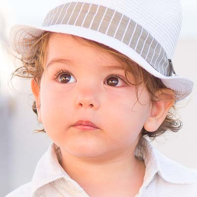 Portrait photograph of a little boy wearing a white hat