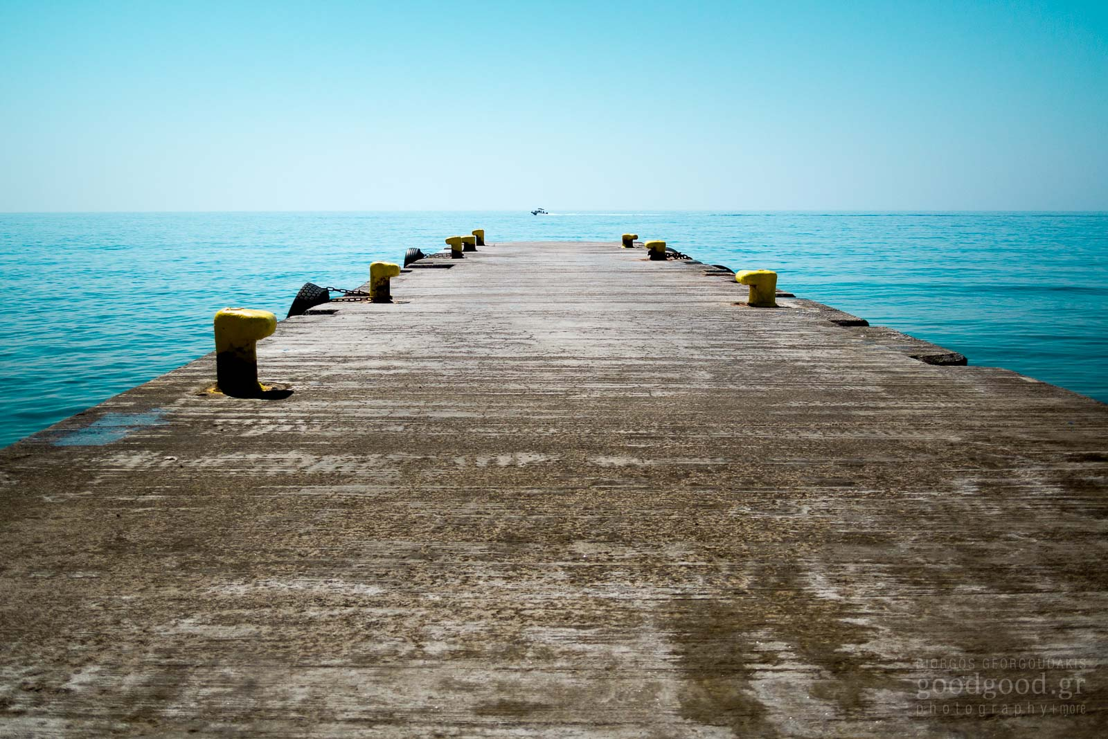 Photograph of a speedboat crossing the horizon in front of a dock
