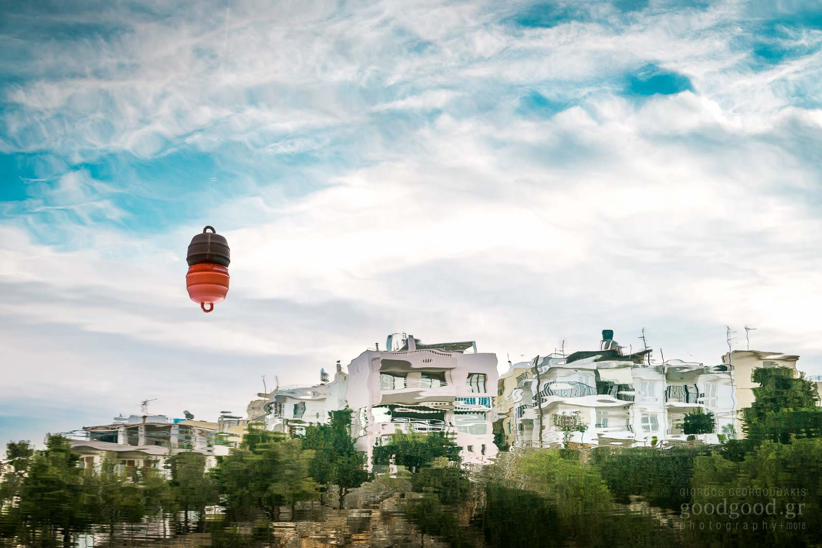 Photo of houses reflection on the water on the lake of Agios Nikolaos near a buoy