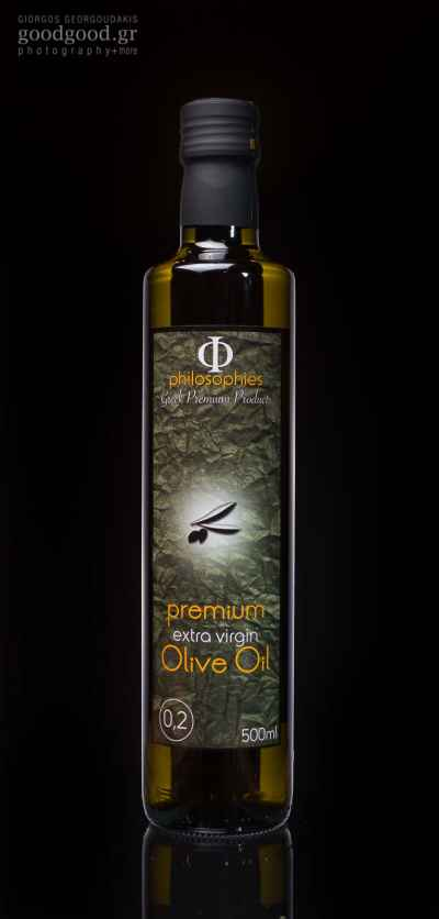 A glass bottle of extra virgin olive oil, photographed in dark background