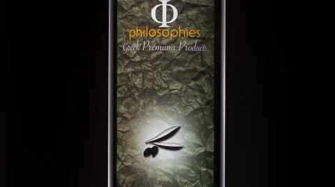Φιάλη έξτρα παρθένου ελαιόλαδου φωτογραφημένη σε σκούρο φόντο