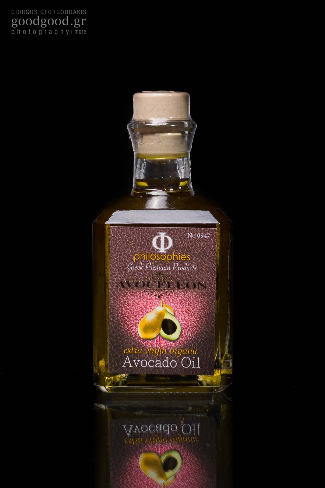 Photograph of a glass bottle of avocado avoceleon oil in dark background