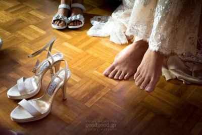 φωτογραφία στην οποία φαίνονται τα παπούτσια της νύφης και τα πόδια της λίγο πριν τα φορέσει