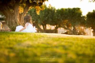 Φωτογραφία βάπτισης ένα κοριτσάκι κάθεται στο γρασίδι κάτω από ένα δέντρο κατά το ηλιοβασίλεμα