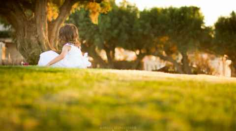 Christening photo of a girl siting on the grass under a tree during the sunset