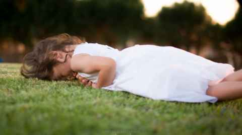 Photo of a girl in a white dress rolling on the grass and laughing