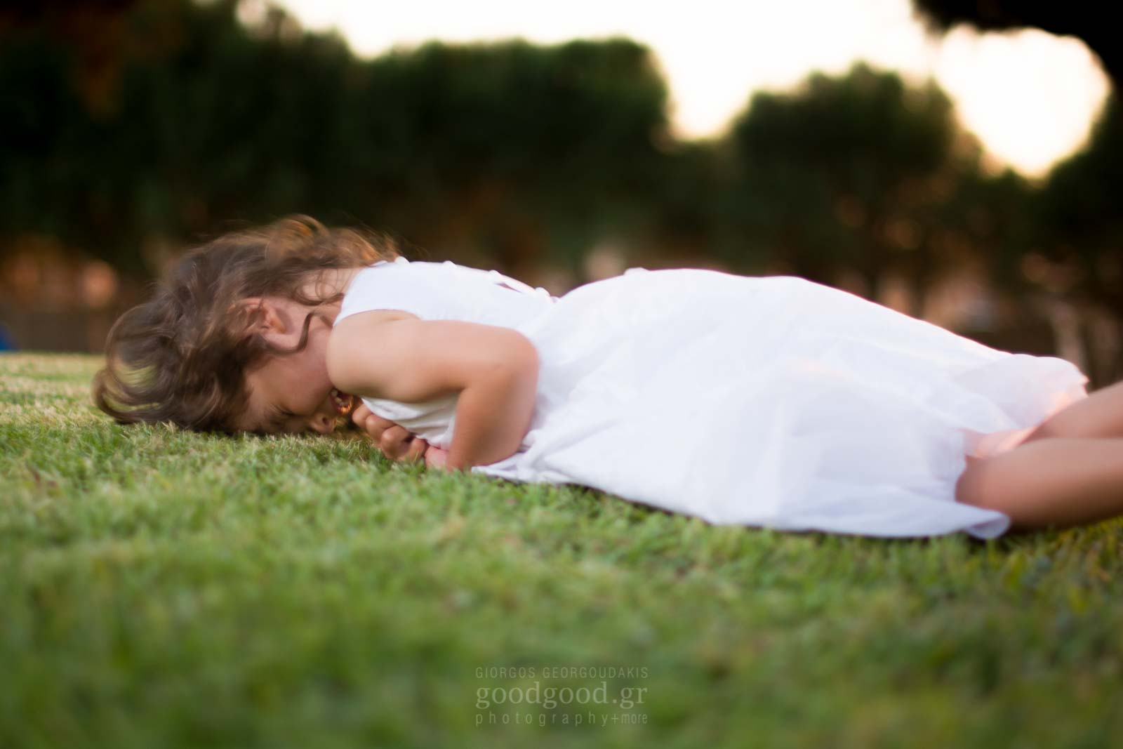 Φωτογραφία ενός μικρού κοριτσιού με λευκό φόρεμα να κυλιέται στο γρασίδι και να γελάει