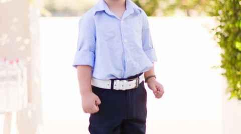 Μικρό αγοράκι ντυμένο για την βάπτιση του ποζάρει για πορτραίτο
