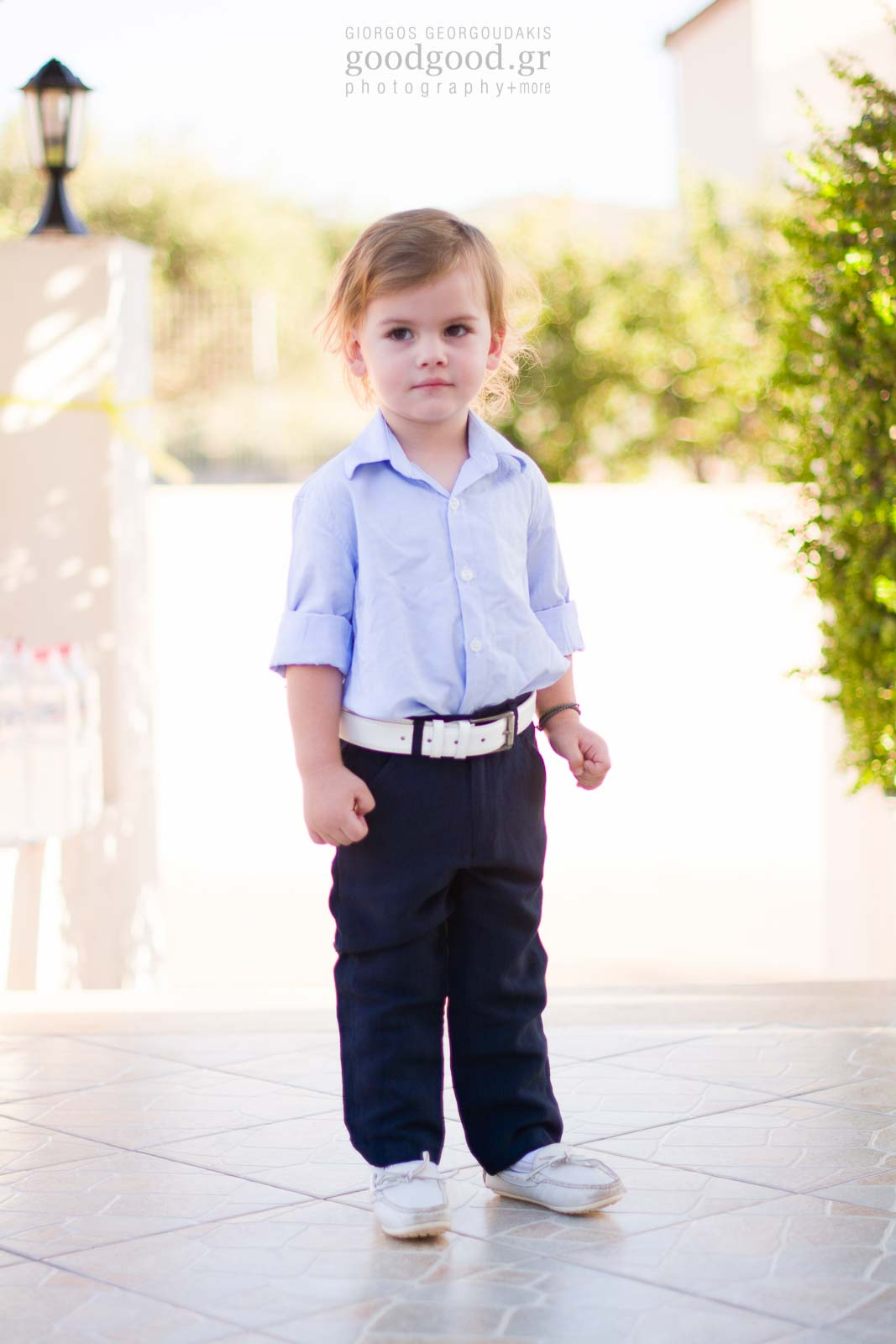 Little boy dressed up for his baptism standing for a portrait