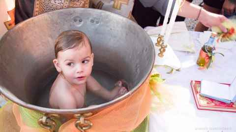 A little boy sitting inside the baptismal font