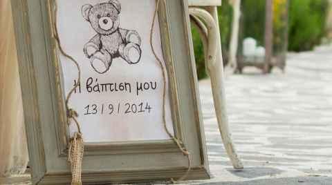 Λούτρινο αρκουδάκι κρέμεται επάνω σε μία πινακίδα καλωσορίσματος σε βάπτιση