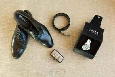 Groom's accesories placed neatly, watch, shoes, belt and cufflinks