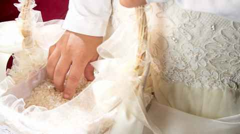 Bridesmaid puts her hand into the rice basket