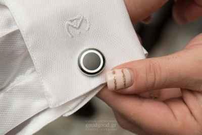Κοντινή φωτογραφία με το χέρι μιας γυναίκας να κρατάει το μανικετόκουμπο του γαμπρού