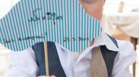Νήπιο παίζει κρυφτούλι κρατώντας μία μικρή πινακίδα μπροστά από το πρόσωπο του