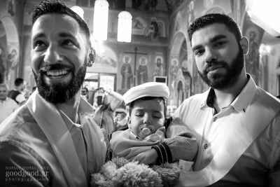 Two godfathers hold a sleeping boy with a pacifier between them, black & white photograph