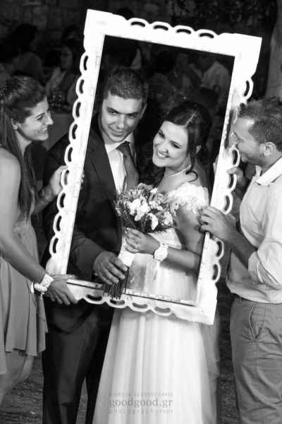 Best man and maid of honnor hold a wooden frame around the newly wed couple