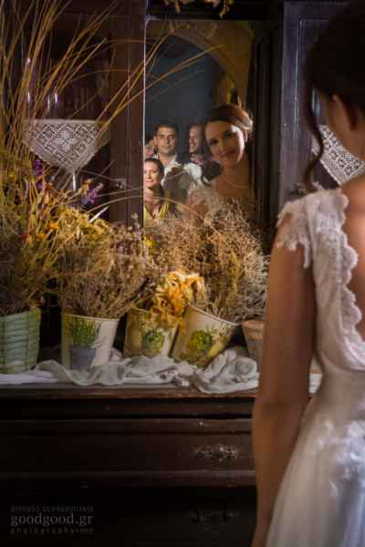 Bride looking at the mirror and while her friend appear in the background