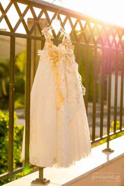 Λευκό φόρεμα βάπτισης κρεμασμένο σε κάγγελα λουσμένο με ήλιο