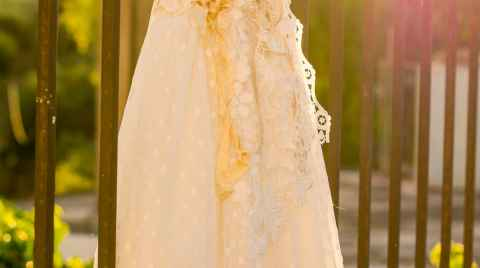 White christening gown hung on railings under the sun