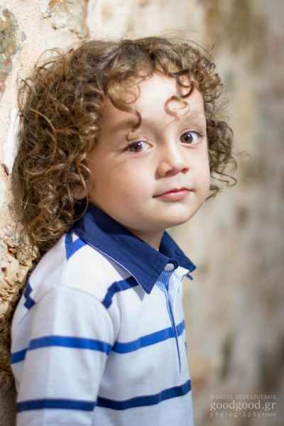 Portrait of a boy with currly hair leaning on the stone wall and looking towards the camera