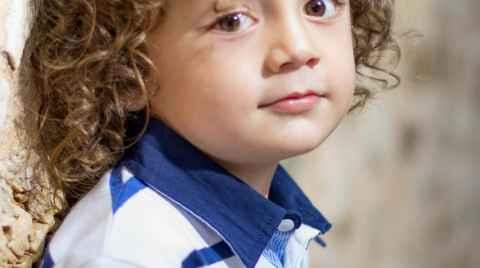 Πορτραίτο ενός αγοριού με σγουρά μαλιά να ακουμπάει την πλάτη του στον πέτρινο τοίχο και να κοιτάει προς τον φακό