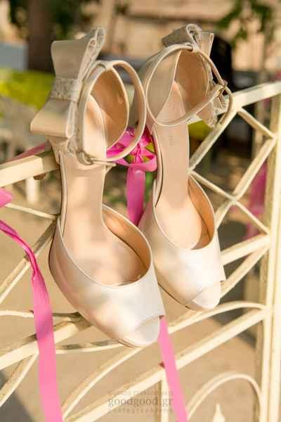 Νυφικά παπούτσια κρεμασμένα σε μία λευκή καγκελόπορτα