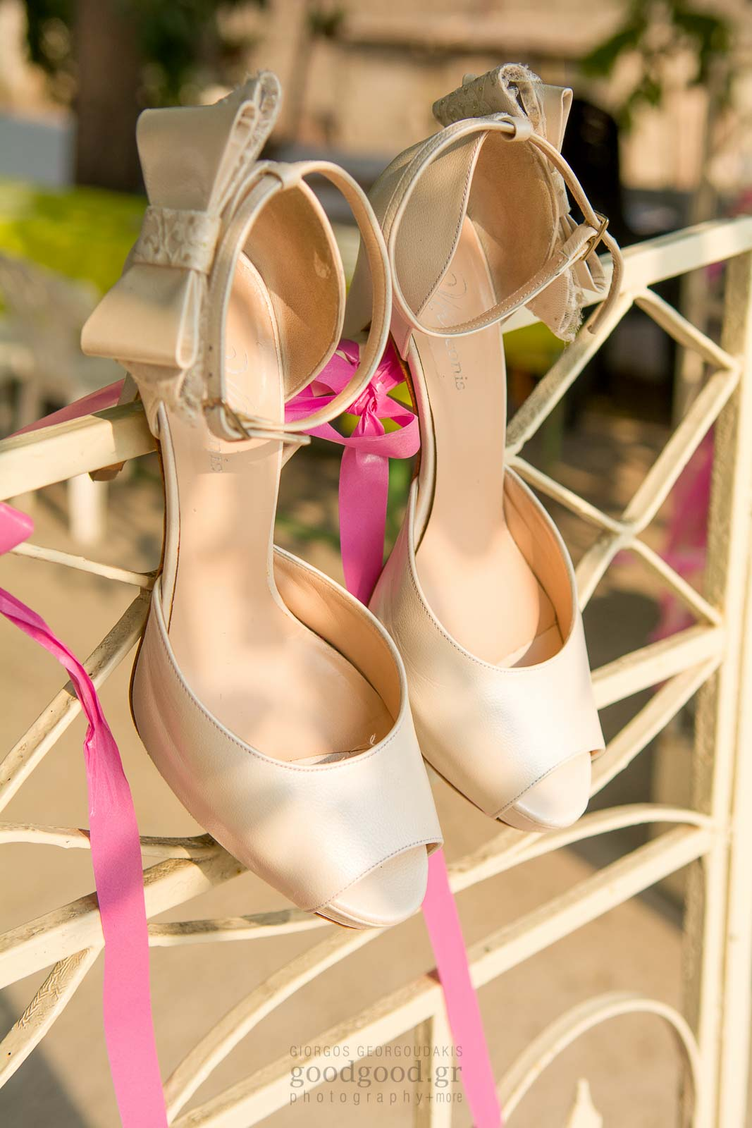 Wedding shoes hanging on a white gate