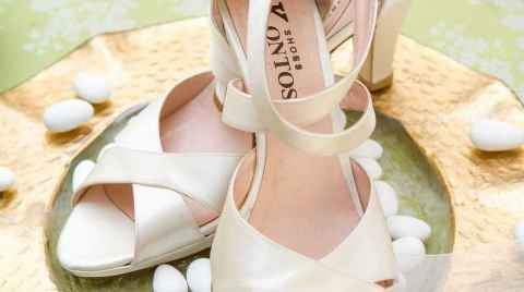 Wedding shoes on a gold plate decorated with sugared almonds - wedding in Messara Iraklio Crete