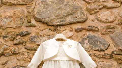 Christening gown hanging on a stone wall
