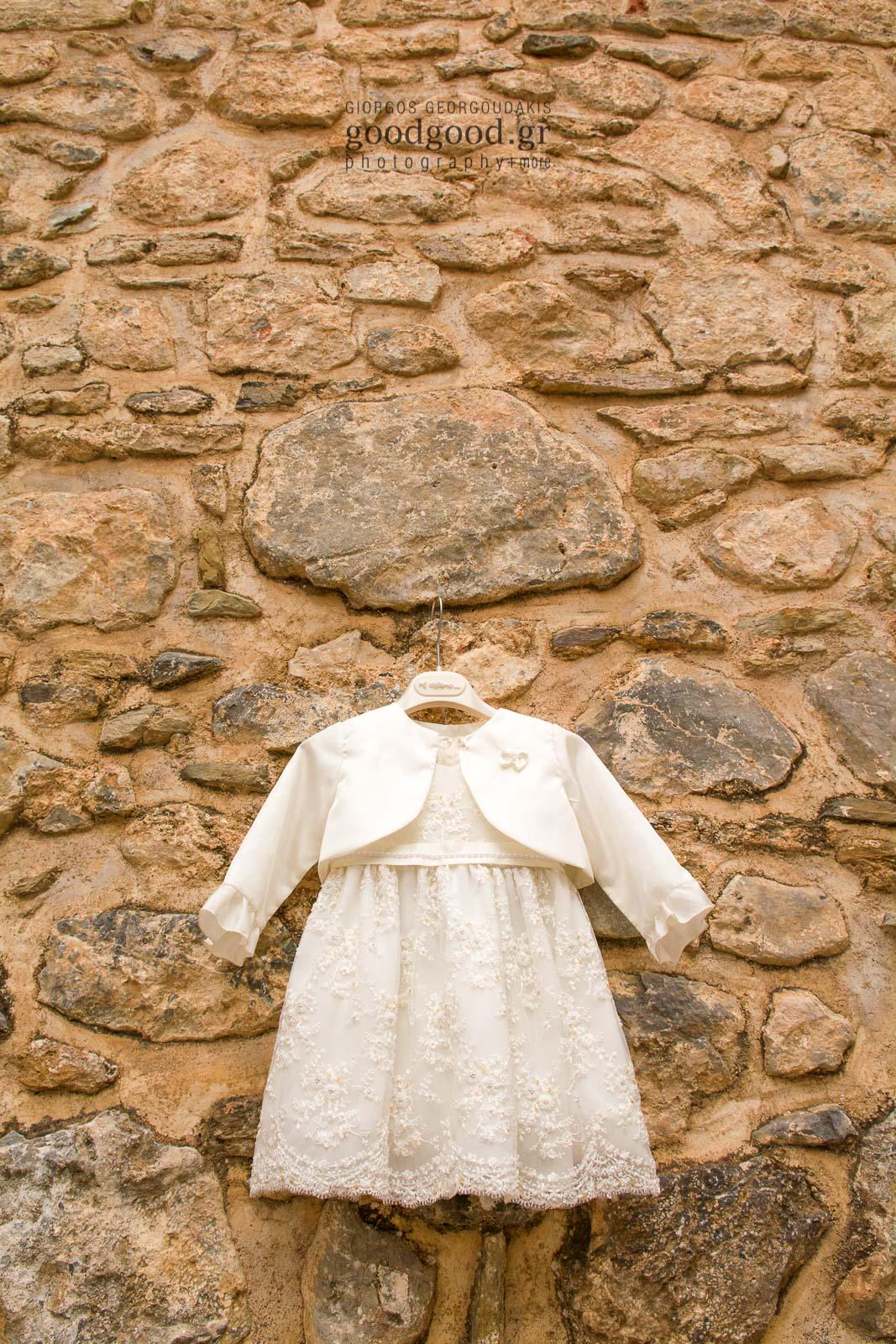 Φόρεμα βάπτισης κρεμασμένο επάνω σε πέτρινο τοίχο