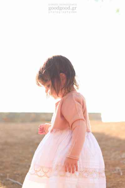 A girl standing in the sunset looking at her feet during a next-day photoshoot of a christening