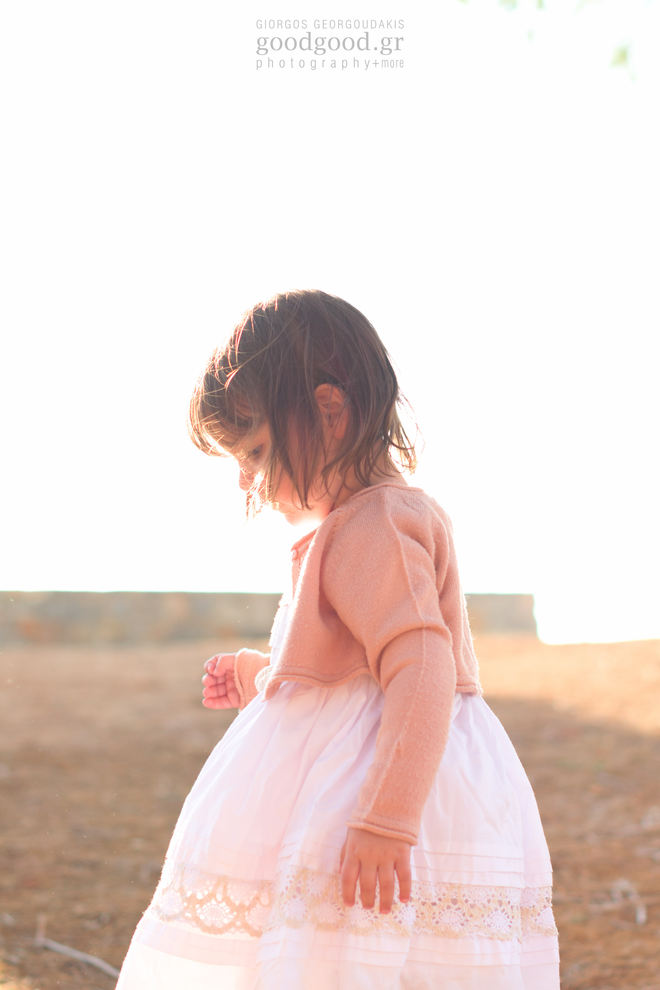 Ένα κοριτσάκι στέκεται στο ηλιοβασίλεμα και κοιτάει το έδαφος σε φωτογράφιση βάπτισης