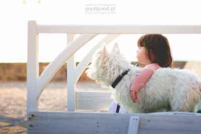 Ένα κοριτσάκι κάθεται στο πρεβάζει αγγαλιά με τον σκύλο της