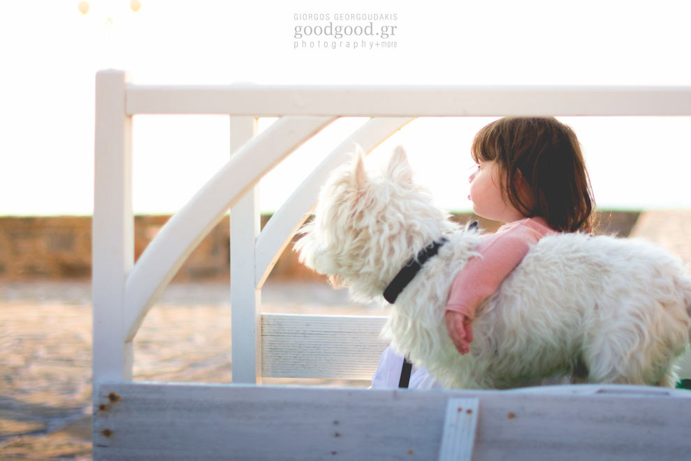 A baby girl sitting on a bench and hugging her dog
