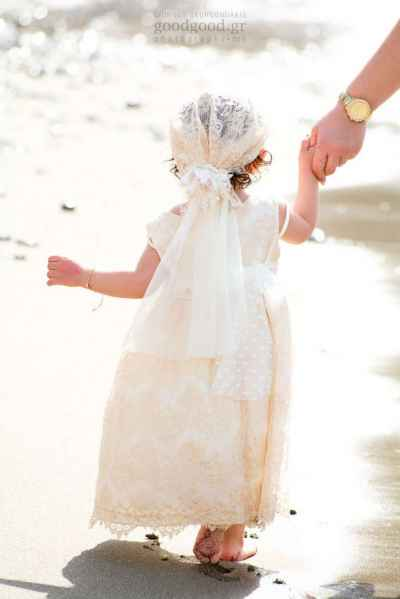 A baptized christened girl is walking on the sand by the beach while holding her godmothers hand