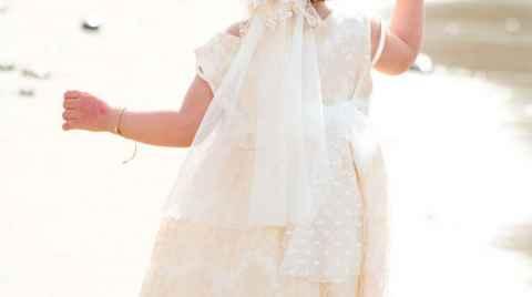 Ένα βαπτισμένο κοριτσάκι περπατάει στην ακροθαλιασσιά κρατόντας το χέρι της νονάς του