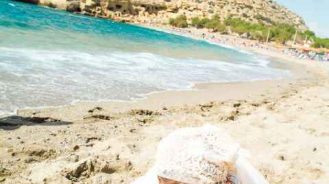 A baptized girls is searching in the sand in Matala Herklion Crete Greece beach